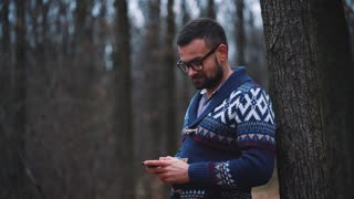 Man in glasses is walking through the autumn forest and using smartphone. Slow motion