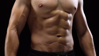 Man shows a muscular strong body close-up on a black background