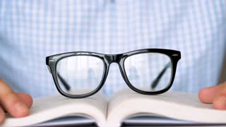 Man takes his glasses and reads a book close up