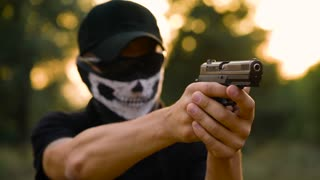 Man with the face closed with a handkerchief and sunglasses getting ready to shoot a gun, close up. Slow motion