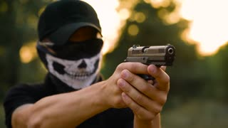 Man with the face closed with a handkerchief and sunglasses getting ready to shoot a gun, close up