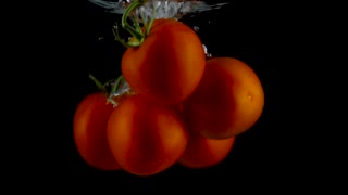 Red tomatoes fall and float in water, black background