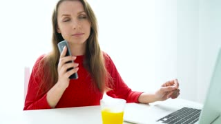 Smiling woman sitting at white home office and talking on smartphone