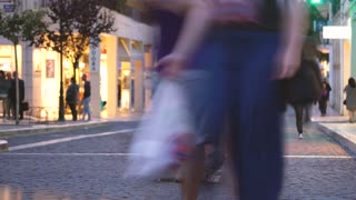 Timelapse of man sitting on crowded evening street while a blur of fast moving people move around him