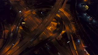 Vertical top down aerial view of traffic on freeway interchange at night, quickly speed