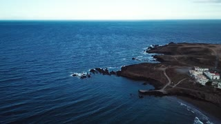 View from the height of rocky coastline with white buildings and a lighthouse on Tenerife, Canary Islands, Spain. Wild Coast of the Atlantic Ocean