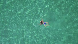 View from the height on swimming woman in the clear sea