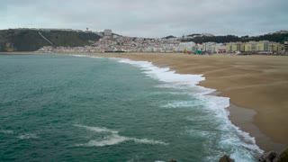 View of Nazare atlantic coast and sandy beach in Portugal. Slow motion