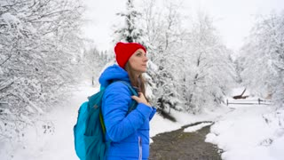 Woman climbs on a snow-covered mountain, turns around. Clear sunny frosty weather