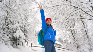 Woman climbs on a snow-covered mountain, turns around, smiling and waving to somebody hand. Clear sunny frosty weather