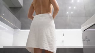Woman entering the shower and dropping her towel
