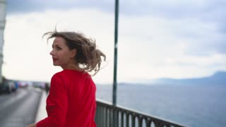 Woman in red dress runs along the waterfront on the sea coast. Slow motion