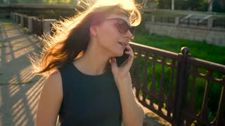 Woman in sunglasses talking on the smartphone while walking down the street at sunset, close up, close-up. Slow motion