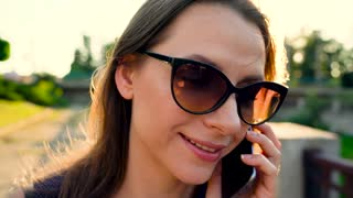 Woman in sunglasses talking on the smartphone while walking down the street at sunset, close up, close-up