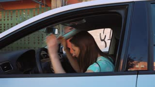 Woman is angry because her car has broken down, throws the key out the window and leaves