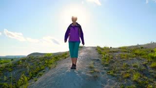 Woman is traveling with a backpack over hilly terrain. Hiking