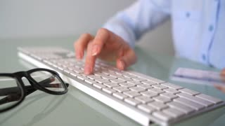 Woman pays by credit card purchases on the Internet. Woman office worker typing on the keyboard. Online payment concept