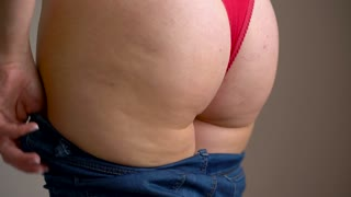 Woman pulls her jeans on her buttocks with cellulite