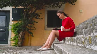 Woman reading an e-book sitting on the steps outdoors