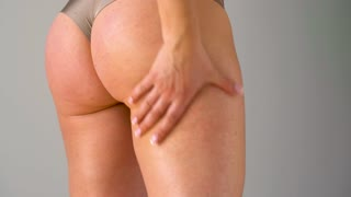 Woman rubs into the skin of the buttocks and legs anti-cellulite cream