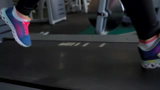 Woman running on treadmill in gym, slow motion