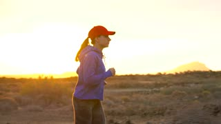 Woman runs along the deserted area at sunset. Mountains on the background.
