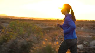 Woman runs along the deserted asphalt road at sunset. Mountains on the background.