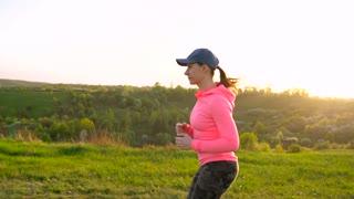Woman runs outdoors at sunset, slow motion