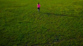 Woman runs through the stadium at sunset, view from the top