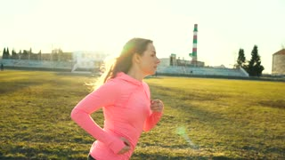 Woman runs through the stadium at sunset