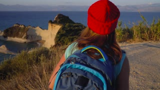 Woman with a backpack makes photo of the Cape Drastis at Corfu island in Greece