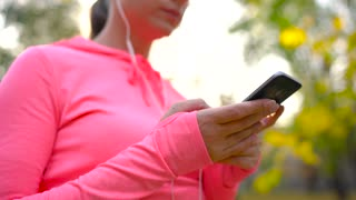 Woman with headphones and a smartphone chooses the music for a run through the autumn park
