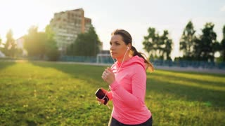 Woman with headphones and smartphone runs through the stadium at sunset