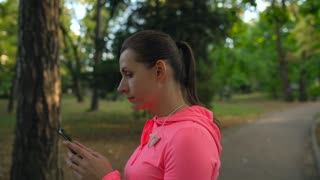 Woman with wireless headphones and a smartphone chooses the music and runs through the autumn park