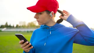Woman with wireless headphones and smartphone chooses music and runs through the stadium at sunset. Slow motion