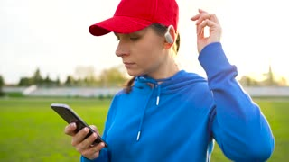 Woman with wireless headphones and smartphone chooses music and runs through the stadium at sunset