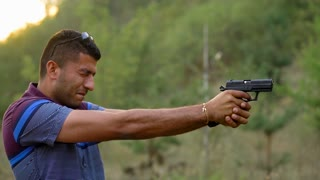 Young arab man is shooting from a gun, close up