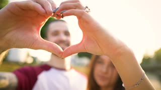 Young couple in love making heart symbol with their hands at sunset. Slow motion