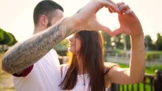 Young couple in love making heart symbol with their hands at sunset
