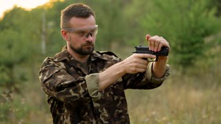 Young man in camouflage shooting from a gun, close up. Slow motion