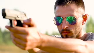 Young man with a gun is aiming to shoot a close up