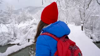 Young woman walks across the bridge across the river and uses a smartphone for make a photos of a beautiful winter snow-covered landscape
