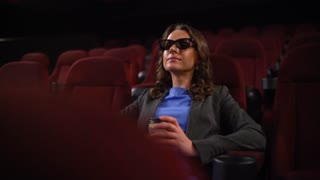 Young woman watches movie 3D at the cinema and drinks coffee, looking at the screen