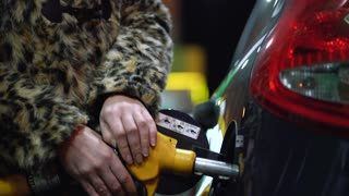 Woman fills petrol into her car at a gas station in winter