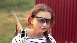 Young beautiful girl in glasses with a gun shooting
