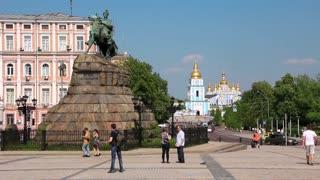 People near monument to Bogdan Khmelnitsky on Sofiyskaya square and Mikhailovsky Golden-Domed Monastery in Kiev, Ukraine