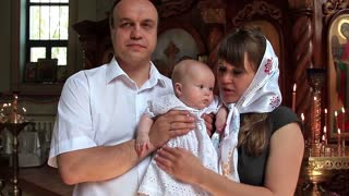 Mother and father with baby in orthodox church after christening ceremony