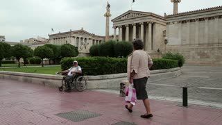 GREECE, ATHENS, JUNE 7, 2013: Destitute disabled person on invalid chair and people on the street near National Assembly building (Academy of Athens)