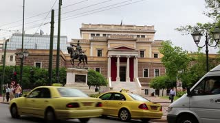 GREECE, ATHENS, JUNE 7, 2013: Road traffic near statue of General Theodoros Kolokotronis and old parliament house in Athens, Greece
