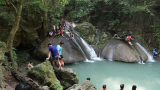 THAILAND, KANCHANABURI PROVINCE, APRIL 5, 2014: People in Erawan National Park and Erawan Waterfall, Kanchanaburi Province in western Thailand